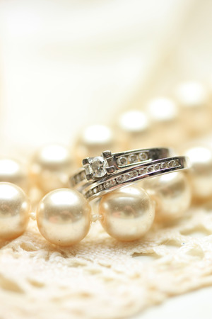 wedding band: Engagement and wedding band with diamonds on a pearl necklace Stock Photo