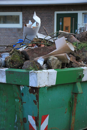 dumpster: Loaded dumpster near a construction site, home renovation