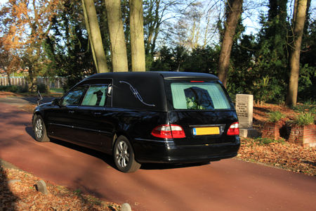 A black hearse on a cemetery in the autumn