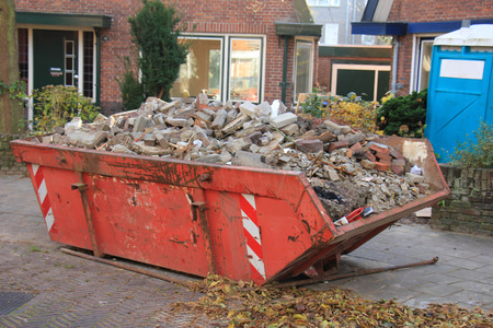 Loaded garbage container near a construction site, home renovation