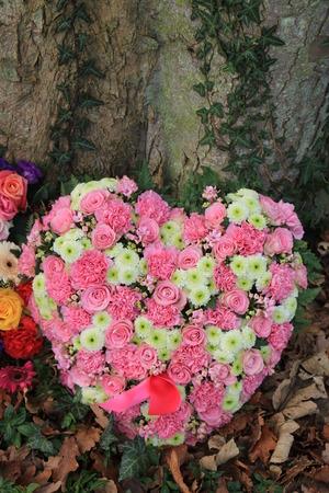 sympathy flowers: Heart shaped sympathy or funeral flowers near a tree