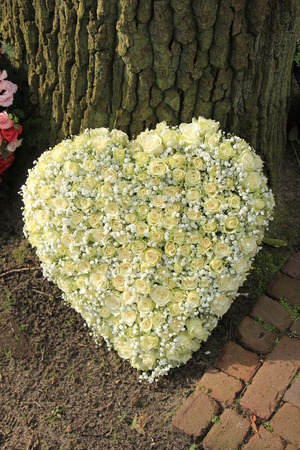 sympathy flowers: A heart shaped funeral flower arrangement, white roses