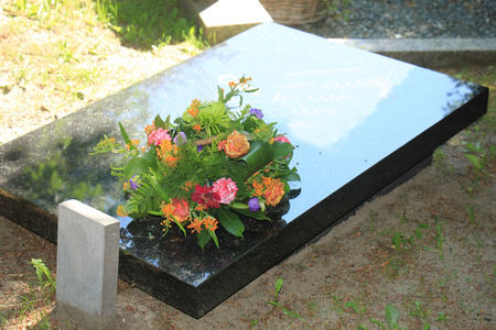 gravestone: Colorful flowers on a black marble gravestone