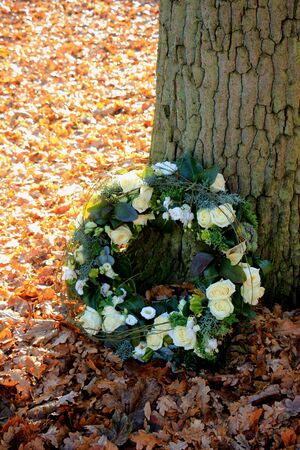 Shaped sympathy or funeral flowers near a tree at a cemetery