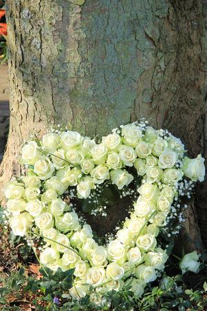 sympathy flowers: Heart shaped sympathy flowers near a tree