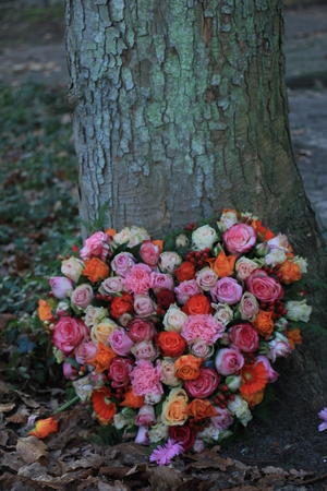 Heart Shaped sympathy or funeral flowers near a tree at a cemetery Stock Photo