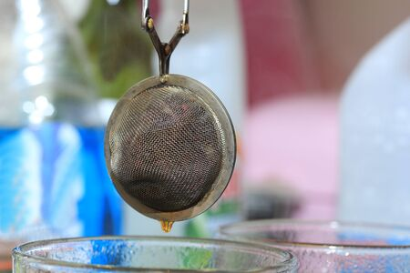infuser: Metal tea infuser with tea dripping out