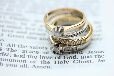 christian marriage: Two wedding sets, one in yellow gold, one in white gold for a double bride wedding on a bible verse Stock Photo