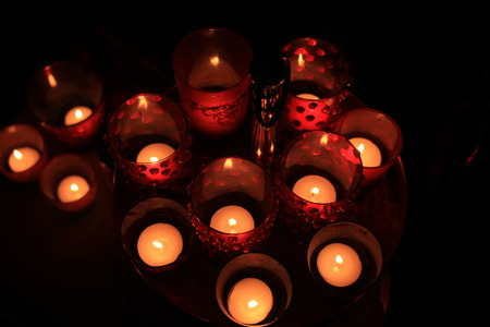 Red candles and votive lights burning in a christmas arrangement