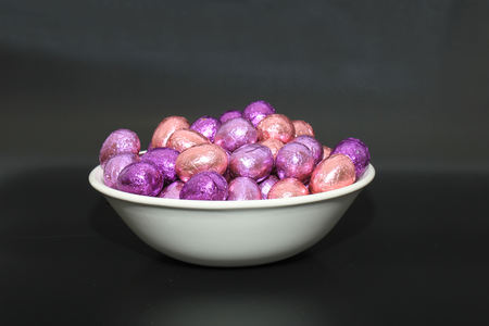 Foil wrapped chocolate easter eggs in a white porcelain bowl