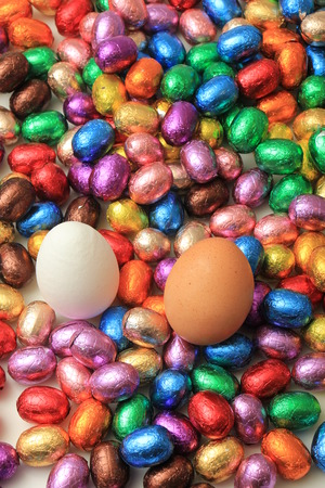 Hen eggs on a pile of colorful wrapped chocolate easter eggs