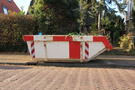 saltar: Contenedor cargado cerca de un sitio de construcción, rehabilitación de viviendas Foto de archivo