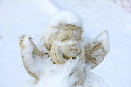 a guardian angel grave ornament in the snow