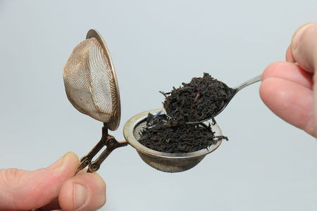 Metal tea infuser with dried tea leaves Stock Photo