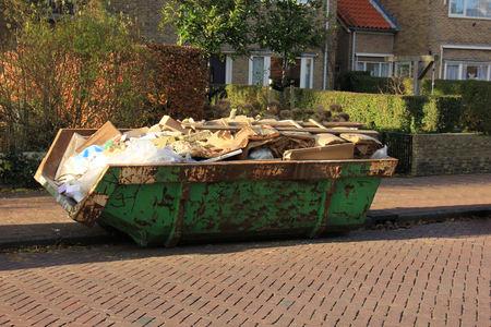 saltar: Cargado basurero cerca de un sitio de construcción, la renovación del hogar