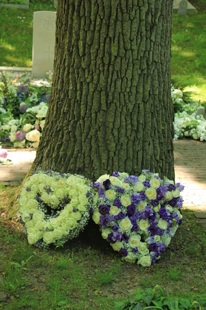 Heart shaped sympathy flowers  in white and purple blue