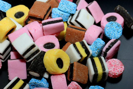 Stacked liquorice all sorts in different shapes, colors and sizes Stock Photo