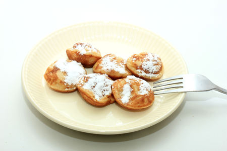 Poffertjes, Dutch small, fluffy pancakes, served with powdered sugar and butter. Stock Photo