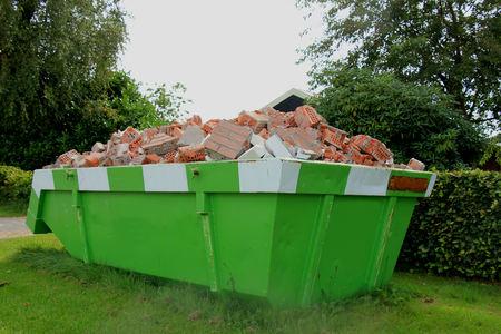 Cargado basurero cerca de un sitio de construcción, la renovación del hogar