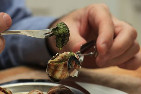 Man eating escargots de Bourgogne using a special tong and a snail fork