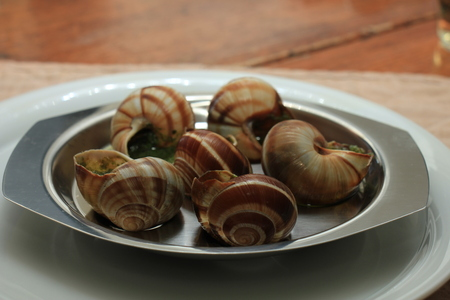 Escargots de Bourgogne on a metal plate, just out of the oven