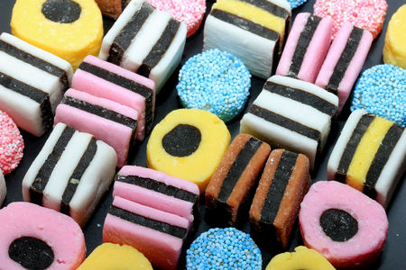 Stacked liquorice all sorts in different shapes, colors and sizes Фото со стока