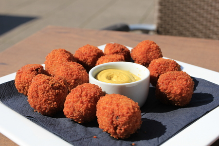 Dutch Bitterballen with mustard, warm stuffed fried meatballs, served in the Netherlands Stockfoto