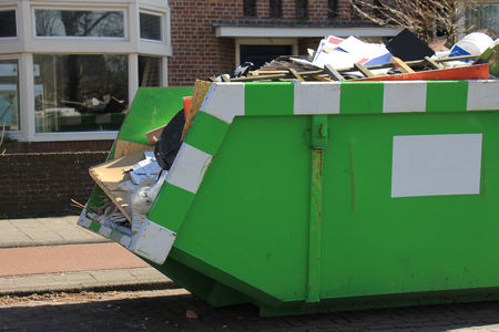 Loaded dumpster near a construction site, a home renovation or maintenance
