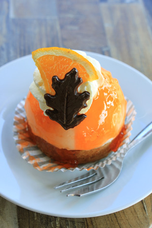Fresh orange mousse confectionery, with cream and a chocolate decoration Imagens