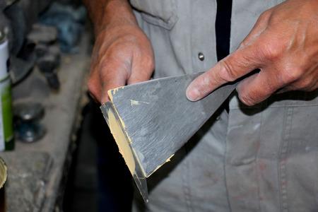 Man preparing filler in a vehicle repair shop Stock Photo