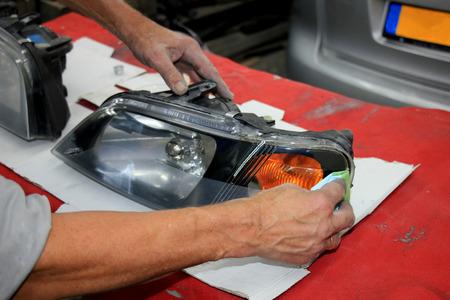 Man refurbishing a car headlight with clear coating 写真素材