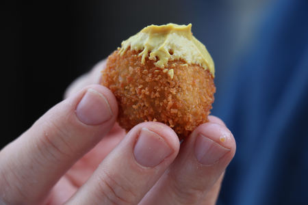 Dutch snack:  Man eating a bitterbal with mustard. Warm stuffed fried meatballs, often served with alcoholic drinks as