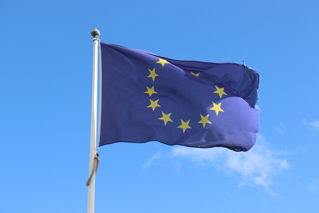 The blue European Union Flag against blue sky, frayed