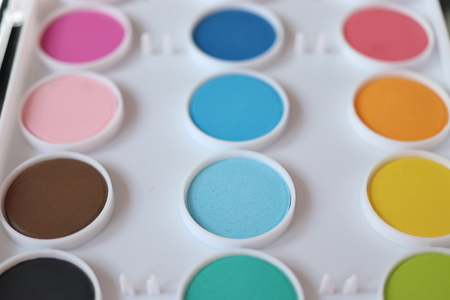 Different colors of waterpaint in a white color box Imagens