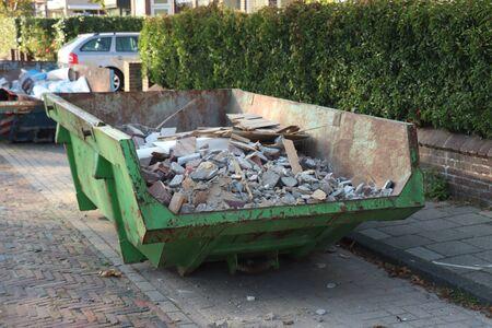 Geladen afvalcontainer of afvalbak in de buurt van een bouwplaats