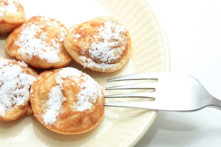 Poffertjes, Dutch small, fluffy pancakes, served with powdered sugar and butter.