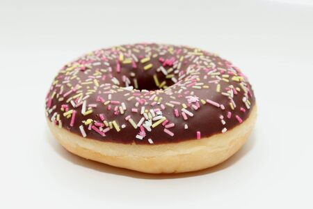 A chocolate iced donut with multicolored sprinkles Foto de archivo