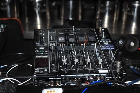 Digital DJ set with equalizer and turntable in a club