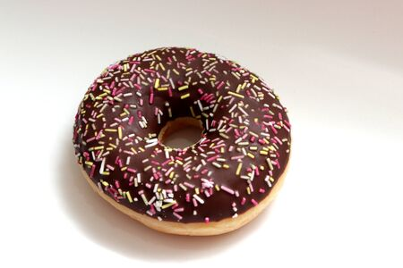 A chocolate iced donut with multicolored sprinkles