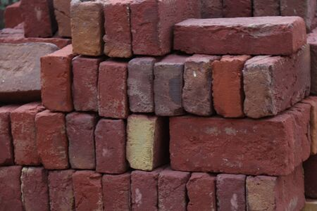 Pile of handmade clay red bricks at a building site Banco de Imagens
