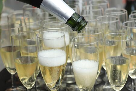 Pouring champagne in stylish glasses, served on a wedding reception