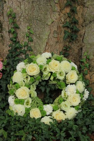 white sympathy wreath or funeral flowers near a tree, white roses and mums 版權商用圖片