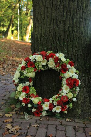 Classic Sympathy wreath near a tree at a cemetery