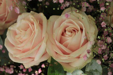 Bridal flower arrangement: Big soft pastel pink roses and various sorts of green decoration