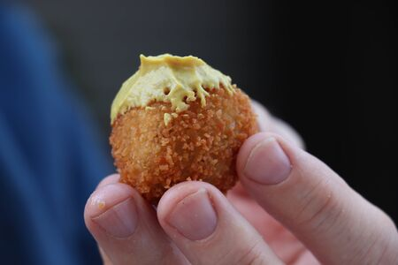 Dutch snack:  Man eating a bitterbal with mustard. Warm stuffed fried meatballs, often served with alcoholic drinks as bittergarnituur, a Dutch name for snacks Stockfoto
