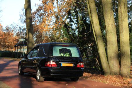 Ein schwarzer Leichenwagen auf einem Friedhof im Herbst