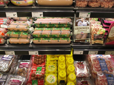 Gieten, The Netherlands - July 28th, 2019:  Different sorts of packaged sausages and cold cuts in a supermarket fridge. Text on tags: product information in Dutch, prices in Euro.