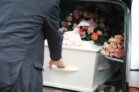 A funeral home employee takes out a white coffin of a hearse