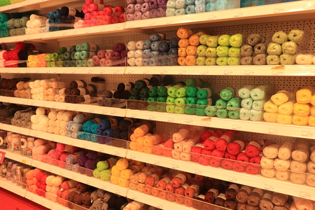 Assen, the Netherlands, July 27th 2019: Multi-colored wool yarns arranged in colors in a shop. Text on labels: special offer, product information and prices in Dutch