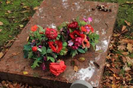 Red funeral flowers on a bron marble tomb